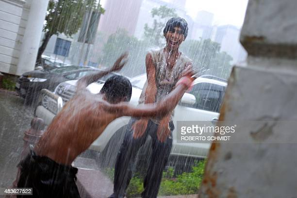 Two Indian boys make the best of a monsoon downpour by playing under a gush of water falling from a rooftop drain in downtown New Delhi on August 11...