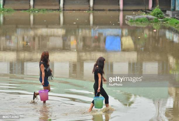 Two Indian girls carrying water in bucket walk passes flood water in a residential area after a heavy rainfall in Dimapur India north eastern state...