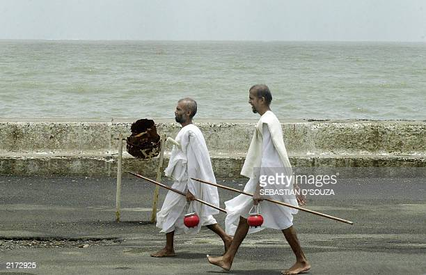 Two Indian Jain monks walk barefoot along the promenade in Bombay 01 July 2003 Jain monks who always walk barefoot spread word of the Jain religion...