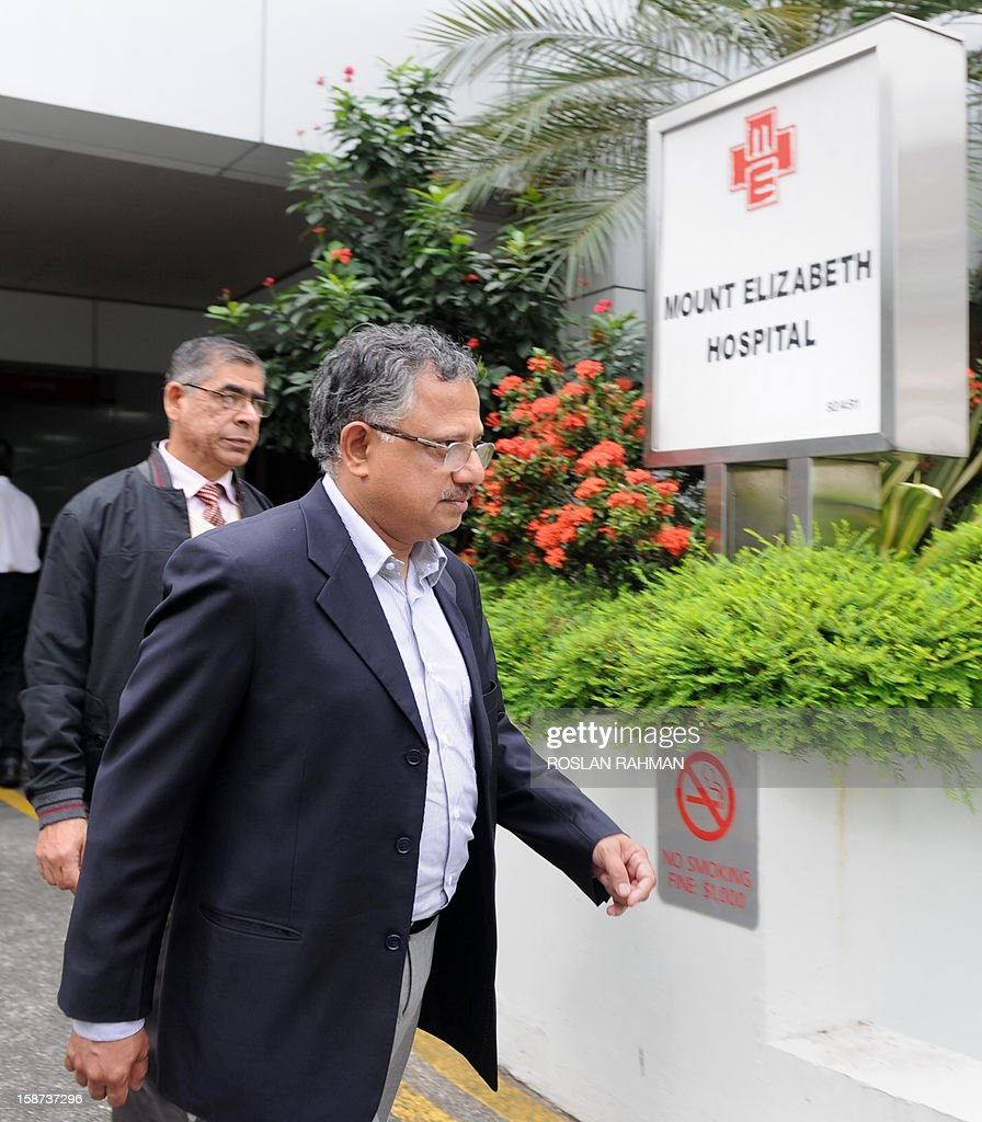 Two Indian officials leave Mount Elizabeth Hospital to board an embassy van in Singapore on December 27, 2012. An Indian student who was left fighting for her life after being brutally gang raped on a bus in New Delhi arrived on December 27 in Singapore for treatment at a leading hospital.
