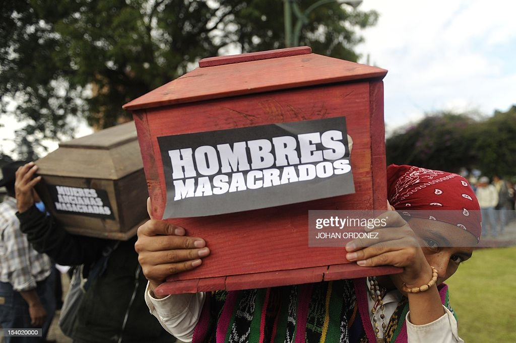 Two indigenous men carry empty coffin in Guatemala city on October 12 in memory of eigth natives killed during clashes between soldiers and...