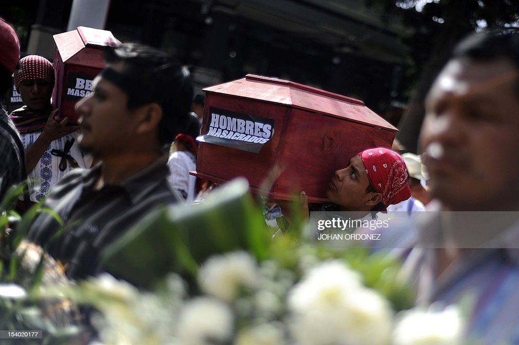 Two indigenous men carry mock coffins during a protest in Guatemala City on October 12 2012 The protest took place as a reaction to the eight...