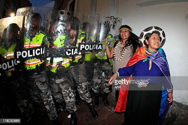 Two indigenous women stand in front of riot policemen during a protest against the exploitation of oil in the Yasuni National Park an incredibly...