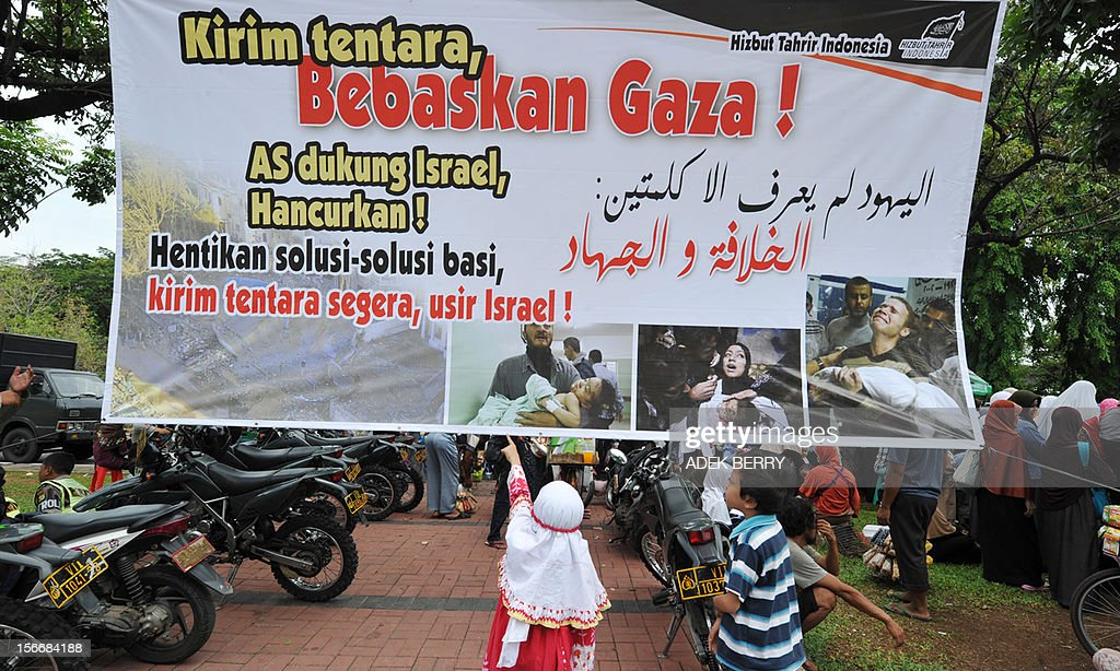 Two Indonesian children look at a banner that reads 'The US supports Israel, Destroy! Stop lip service solution, send troops soon, oust Israel' during a protest against the Israel and US governments and against fresh Israeli air strikes on the Gaza Strip, outside the US embassy in Jakarta on November 19, 2012. Indonesia, the world's most populous Muslim nation, with 240 million people, is a strong supporter of the Palestinian cause.
