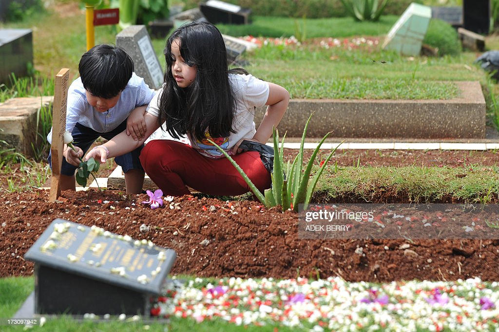 Two Indonesian children place a white rose on a grave at a cemetary as Muslims in the country follow a tradition of visiting the graves of loved ones ahead of the holy month of ramadan, in Jakarta on July 7, 2013. Ramadan is a holy month celebrated by Muslims worldwide marked by fasting, abstaining from foods, sex and smoking from dawn to dusk for soul cleansing and strengthening the spiritual bond between them and the Almighty.