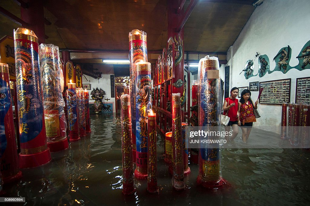 Two Indonesian Chinese women (R) wade through flood waters caused by monsoon rains two days previously past large candles burning at a temple to mark the first day of the Lunar New Year in Sidoarjo on February 8, 2016. After decades of repression under the dictatorship of Suharto, who rose to power after a bloody purge of communists and Chinese in the late 1960s, Chinese-Indonesians are now accepted in mainstream society of the largely Muslim nation, with the Lunar New Year - this year marking the Year of the Monkey - a public holiday where it is known as 'Imlek'. AFP PHOTO / JUNI KRISWANTO / AFP / JUNI KRISWANTO