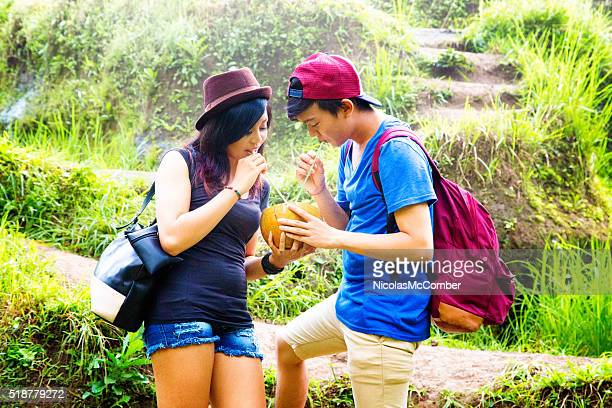 Two Indonesian friends enjoying coconut in terraced rice paddy