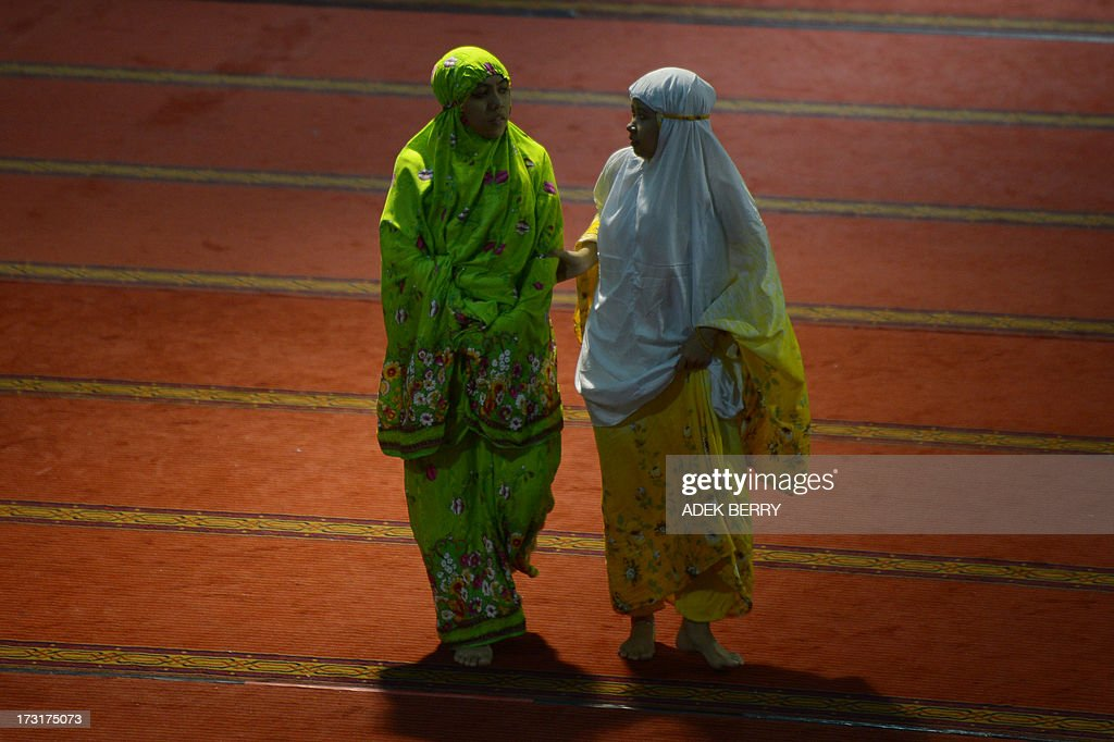 Two Indonesian girls walk prior to night prayers on the first night of the holy month of Ramadan at the Istiqlal mosque in Jakarta on July 9, 2013. Islam's holy month of Ramadan is celebrated by Muslims worldwide marked by fasting, abstaining from foods, sex and smoking from dawn to dusk for soul cleansing and strengthening the spiritual bond between them and the Almighty. AFP PHOTO / ADEK BERRY