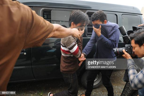 Two Indonesian men arrive for their trials at a shariah court in Banda Aceh on May 17 2017 A sharia court on May 17 sentenced two men to be publicly...