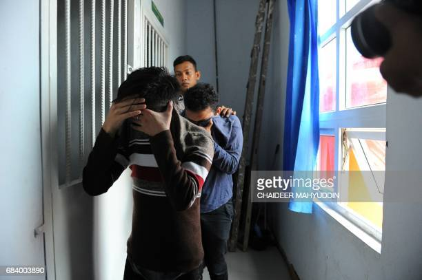 Two Indonesian men walk into a cell prior to their trials at a shariah court in Banda Aceh on May 17 2017 A sharia court on May 17 sentenced two men...