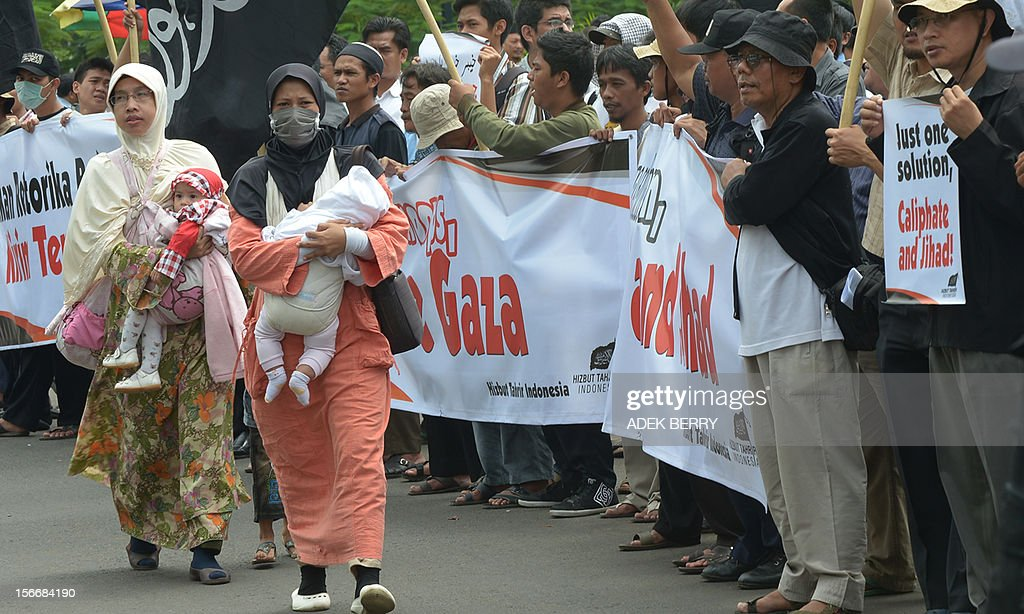 Two Indonesian Muslim women (L) with their children walk past hardline Muslim activists from the Indonesian branch of pro-Caliphate organisation Hizb ut-Tahrir Indonesia (HTI) shouting slogans against the Israel and US governments outside the US embassy in Jakarta on November 19, 2012 as hundreds protested against fresh Israeli air strikes on the Gaza Strip. Indonesia, the world's most populous Muslim nation, with 240 million people, is a strong supporter of the Palestinian cause.
