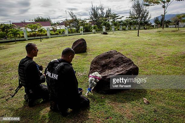 Two indonesian police pray at mass grave to commemorate the tenth anniversary of the Boxing Day tsunami on December 26 2014 in Banda Aceh Indonesia...