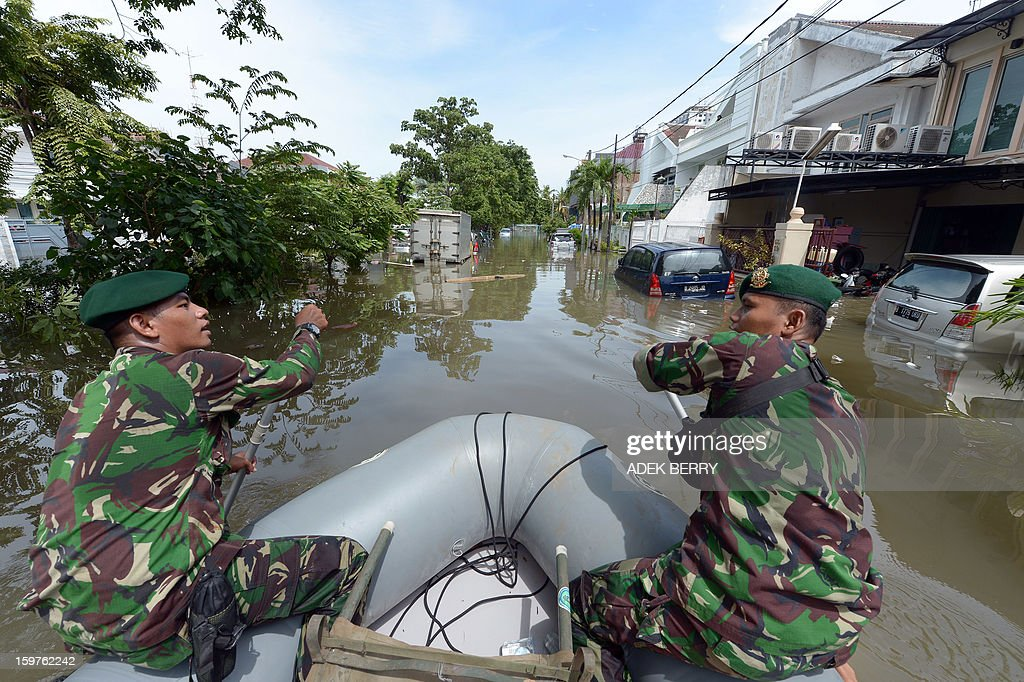 Two Indonesian soldiers paddle a rubber dingny down a flooded street as they conduct a search and evacuation operation at a luxury housing complex in Jakarta on January 20, 2013. The death toll from floods in Indonesia's capital Jakarta rose to 15 on January 19 after rescuers found another four bodies. The floods are the worst to hit the capital since 2007 and forced 18,000 people from their homes.