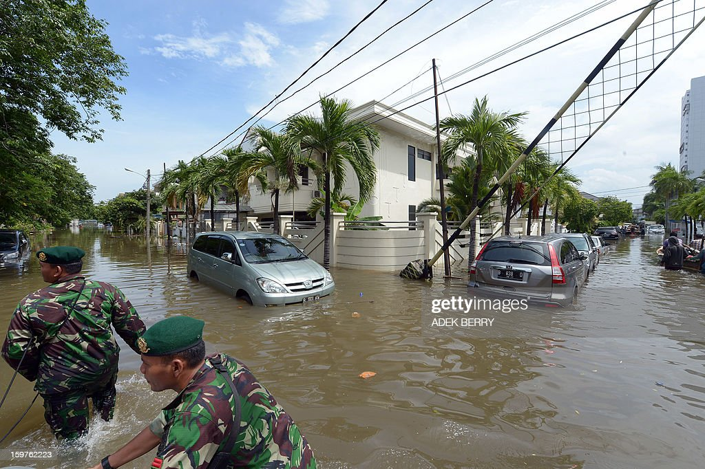 Two Indonesian soldiers pull a rubber boat (out of frame) as they wade past cars inundated by floodwaters at a luxury housing complex in Jakarta on January 20, 2013. The death toll from floods in Indonesia's capital Jakarta rose to 15 on January 19 after rescuers found another four bodies. The floods are the worst to hit the capital since 2007 and forced 18,000 people from their homes. AFP PHOTO / ADEK BERRY