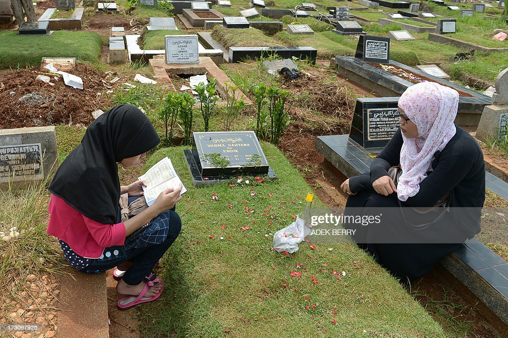 Two Indonesian women pray at a cemetary as Muslims in the country follow a tradition of visiting the graves of loved ones ahead of the holy month of ramadan, in Jakarta on July 7, 2013. Ramadan is a holy month celebrated by Muslims worldwide marked by fasting, abstaining from foods, sex and smoking from dawn to dusk for soul cleansing and strengthening the spiritual bond between them and the Almighty.