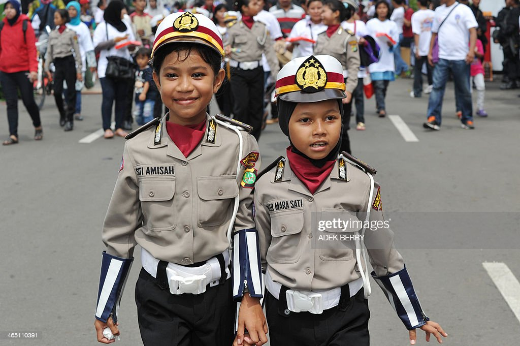 Two Indonesian young girls dressed in police uniforms participate in the launch of a road traffic safety program in Jakarta on January 26, 2014. According to the World Health Organization, an estimated 1.2 million people are killed each year in traffic accidents and in Indonesia more than 25,000 people were killed in 2013 due to traffic compare to 27,000 the previous year. AFP PHOTO / ADEK BERRY