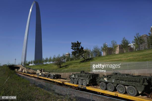 Two Interim Armored Vehicle Strykers sit on a US Army equipment train passing by the Gateway Arch in St Louis Missouri US on Tuesday April 25 2017...