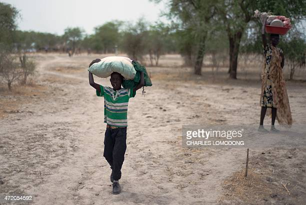 Two Internally Displaced People carry belongings on their heads in Kuernynag in Jonglei State which borders Upper Nile State and Unity State on May 2...