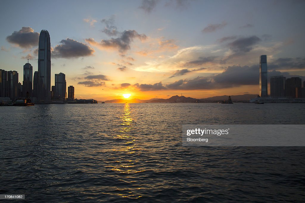 Two International Finance Center (IFC), fifth left, and the International Commerce Centre (ICC), third right, stand on opposite sides of Victoria Harbor as the sun sets in Hong Kong, China, on Tuesday, June 18, 2013. A shortage of housing, low mortgage costs and a buying spree by mainland Chinese have led home prices to more than double since the beginning of 2009, shrugging off repeated attempts by the government to curb gains amid an outcry over affordability. Photographer: Jerome Favre/Bloomberg via Getty Images