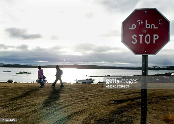 Two Inuit children return from school past a stop sign written in English and Inuit 02 October 2002 in Iqaluit northern Canada Iqaluit is the capitol...