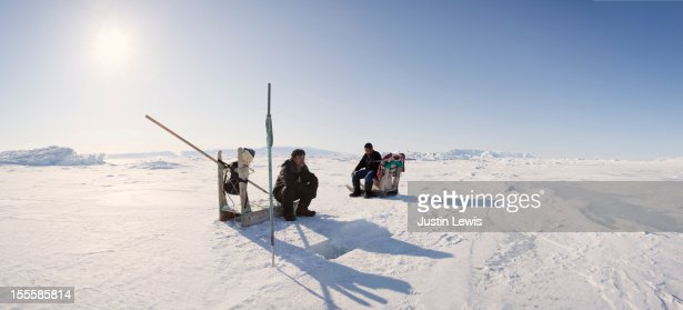 Two Inuit man rest while digging fish hole in ice : Stock Photo
