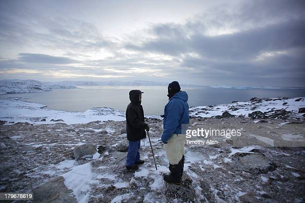 Two Inuit men talk by the sea in mid winter