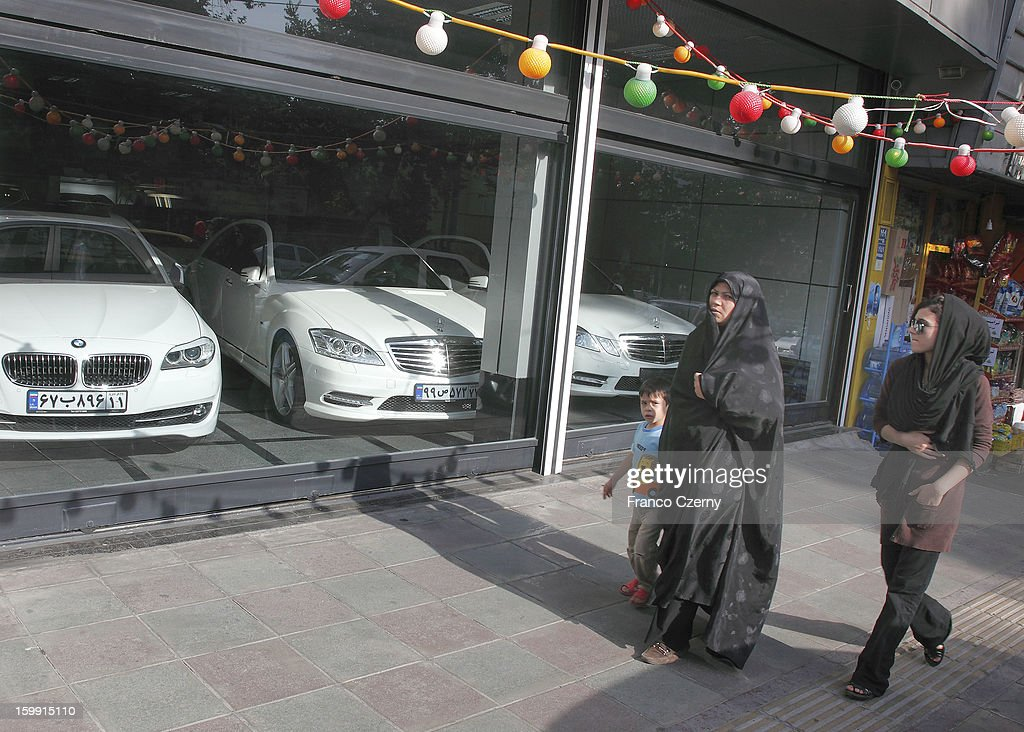 Two iranian women in chadors and a child walk past a car dealer with used BMW and Mercedes Benz cars on August 28, 2012 in Tehran, Iran.