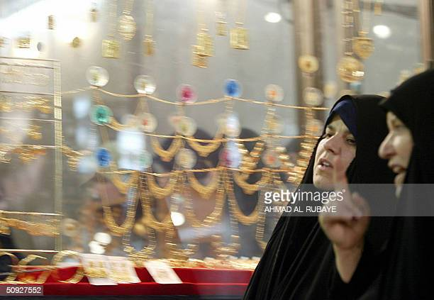 Two Iraqi women chat as they walk past a jewelry shop in the holy city of Najaf some 120 kms south of Baghdad 05 June 2004 US forces have agreed to...