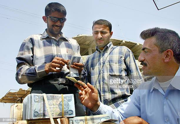 Two Iraqis exchange Iraqi Dinar for US Dollars at a street stall in Basra southern Iraq 30 March 2004 Ahmed Chalabi acting president of the...