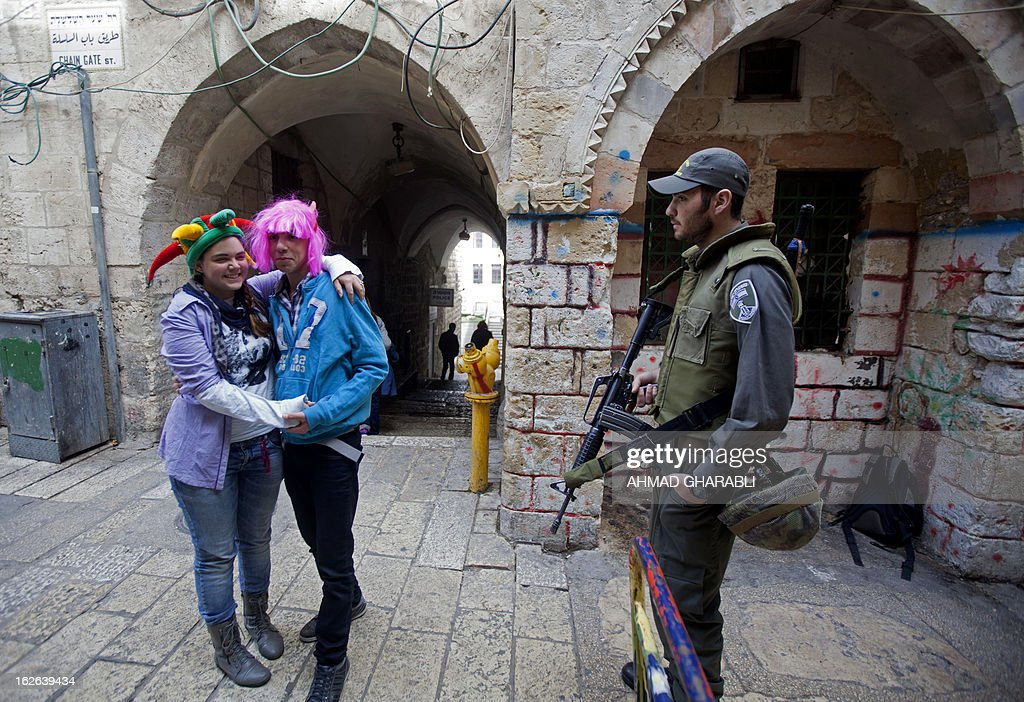 Two Israeli dressed up to celebrates the Jewish holiday of Purim speak with a member of the Israeli security forces outside the Al-Aqsa mosque compound in Jerusalem's old city, as Israeli settlers tried to enter the compound on February 25, 2013. Palestinian president Mahmud Abbas said that Israel was deliberately seeking to stoke unrest in the occupied West Bank but that Palestinians would not be provoked.