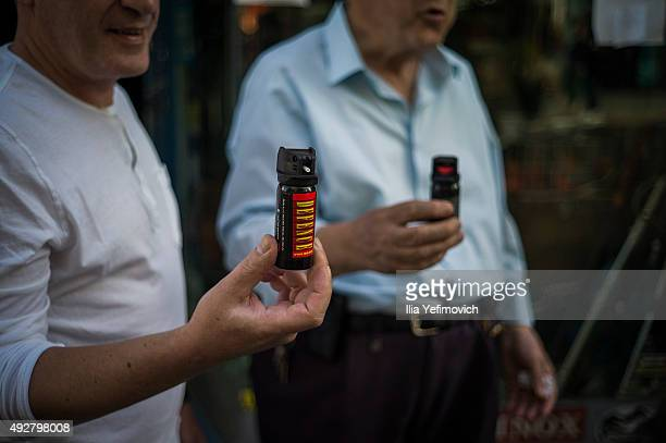 Two Israeli men pose for a portrait as they hold pepper spray on October 15 2015 in Jerusalem Israel Israeli citizens are growing fearful for their...