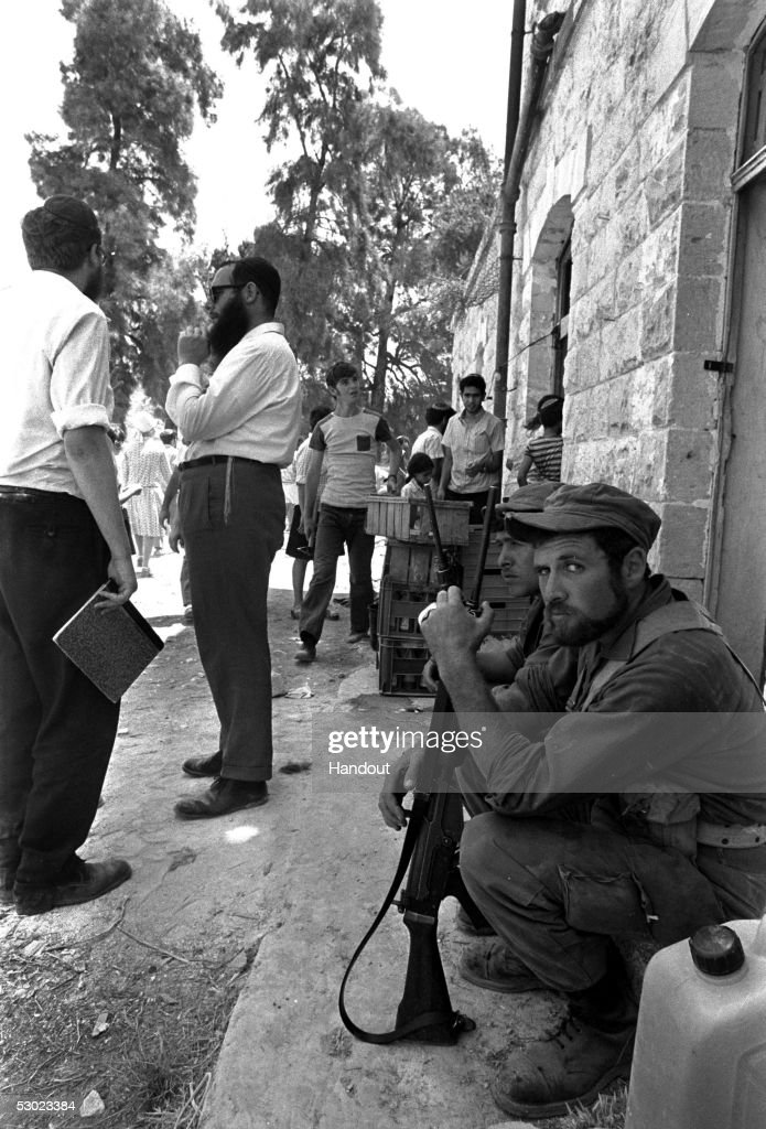 Two Israeli soldiers are deployed to guard right-wing Jewish settlers who have fenced in the old railway station in an initial attempt to make their home July 26, 1974 at Sebastia near the Palestinian town of Nablus in the northern West Bank. After being forcibly evacuated by the Israeli army seven times since the Summer of 1974, the pioneering West Bank settlers' dream was finally realized when they received government permission to move their settlement of Elon Moreh to a nearby Israeli army base in December 1975.