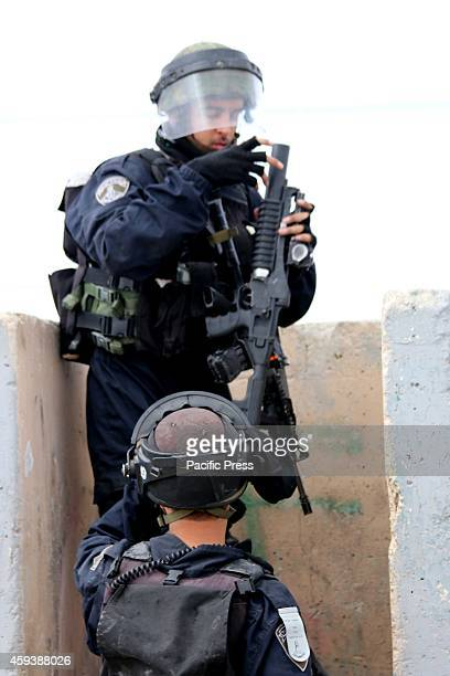 Two Israeli soldiers beside a cement barrier loading their tear gas guns ready to clash with Palestinian protesters at the Qalandia checkpoint an...