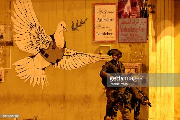 Two Israeli soldiers take cover behind a wall with the famous dove of peace by Banksy in the Bethlehem streets After several days of calmness in the...