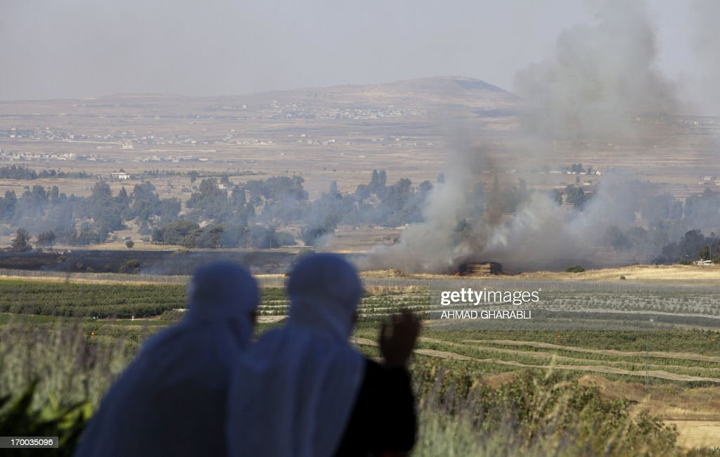 Two IsraeliDruze women look from the Israeli side at the IsraelSyria ceasefire line in the Golan Heights at smoke rising where clashes appeared...