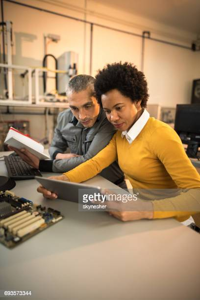 Two IT engineers using e-reader while working in a tech laboratory.