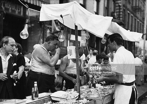 Two Italian American men wearing a singlet eating at a food stall of Little Italy market New York 1950s