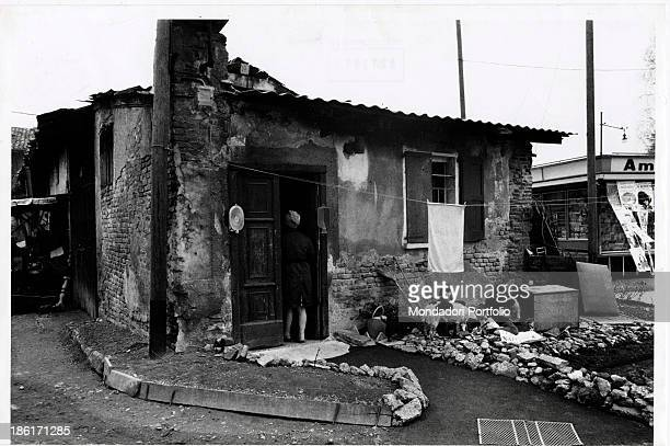 Two Italian children playing with a two dogs in front of a shack in Porta Vigentina Milan 1973