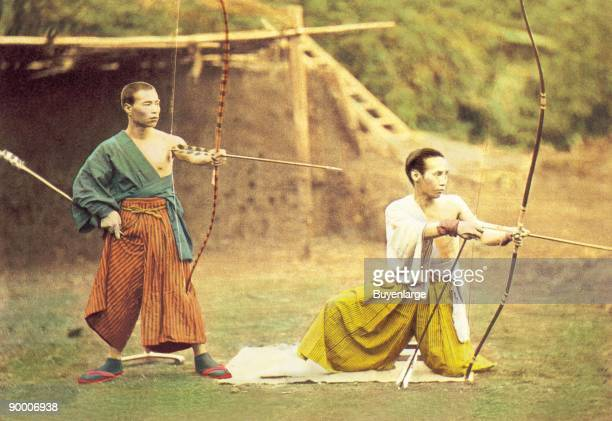 Two Japanese archers take aim at a target