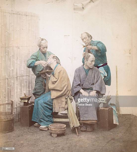 Two Japanese barbers tend to their customers shaving their faces and the tops of their heads and tying their hair in a topknot circa 1865