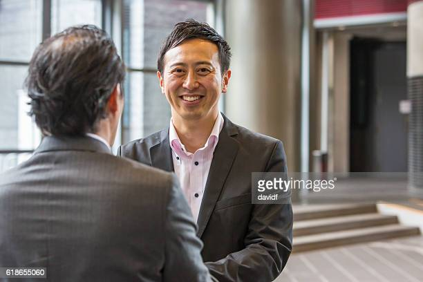 Two Japanese Business Men Meeting in a Kyoto Office Foyer