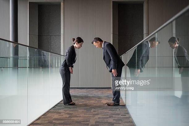 Two Japanese business people bowing towards each other