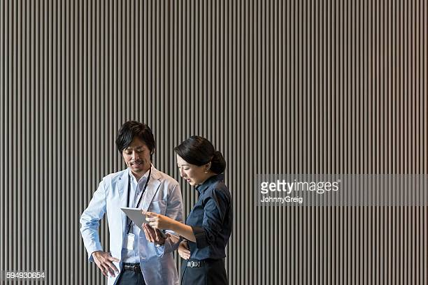 Two Japanese business professionals with digital tablet against textured background