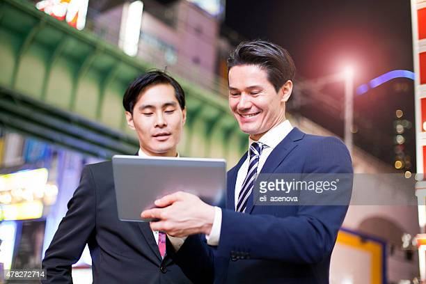 Two Japanese businessmen in Tokyo with digital tablet