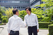 Two Japanese businessmen shaking hands outdoors
