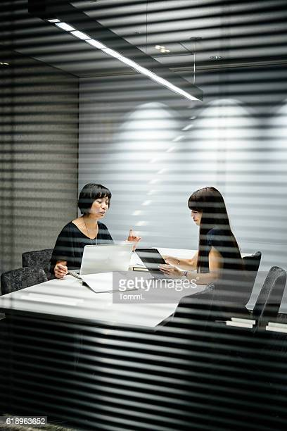 Two japanese businesswomen sitting in a conference room