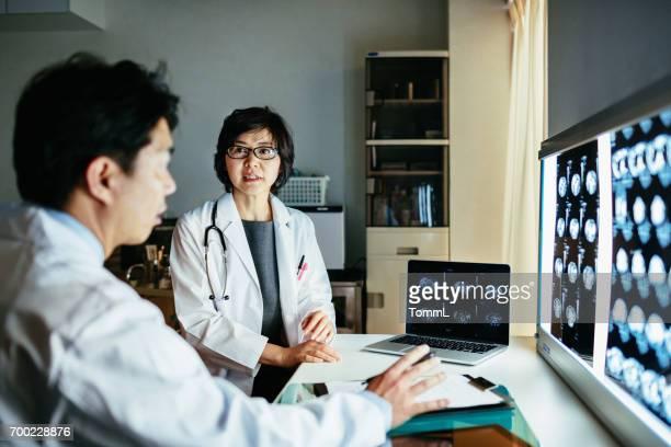 MRI スキャンを議論する 2 つの日本人医師