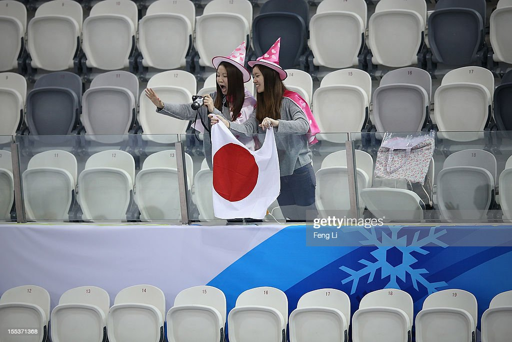 Two Japanese fans hold the national flag and waves to gold medalist Tatsuki Machida of Japan during the medal ceremony of Cup of China ISU Grand Prix of Figure Skating 2012 at the Oriental Sports Center on November 3, 2012 in Shanghai, China.
