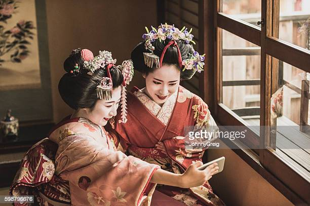 Two Japanese maiko in kimonos using smartphone to take selfie