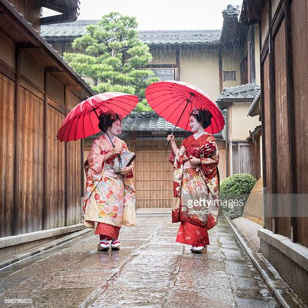 Two Japanese maiko walking in traditional street with umbrellas